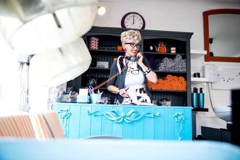 Woman at reception desk of quirky hair salon - CUF10969