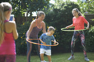 Girl photographing mother and siblings hoola hooping in garden - CUF11107