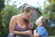 Boy and mother sharing fresh smoothie in garden - CUF11188
