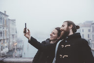 Couple taking smartphone selfie over misty canal, Venice, Italy - CUF11263