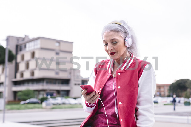 Mature woman in baseball jacket listening to headphones and looking at smartphone - CUF11284