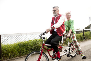 Quirky couple sightseeing on tandem bicycle, Bournemouth, England - CUF11290