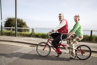 Quirky couple sightseeing on tandem bicycle, Bournemouth, England - CUF11293