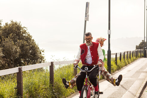 Quirky couple sightseeing on tandem bicycle, Bournemouth, England - CUF11299