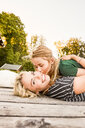 Mother and daughter lying on wooden decking outdoors - CUF11335