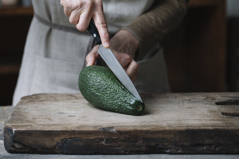 Woman slicing avocado on chopping board, mid section - CUF11386