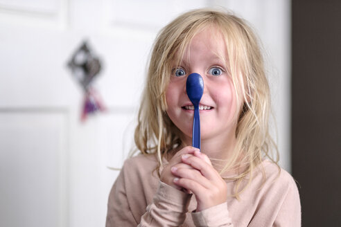 Portrait of smiling little girl playing with blue spoon - HAMF00316