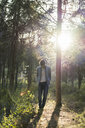 Young man standing in forest, against the sun - AFVF00471