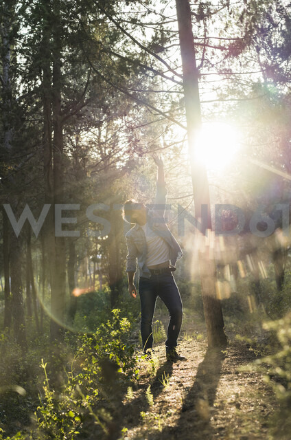 Young man standing in forest, against the sun - AFVF00474