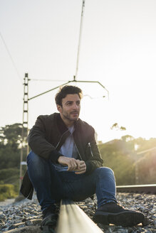 Young man sitting on railroad track - AFVF00477