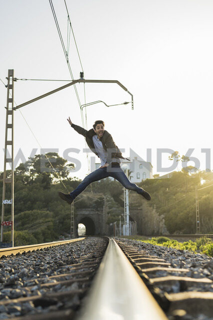 Young man jumping into the air, railroad track - AFVF00480