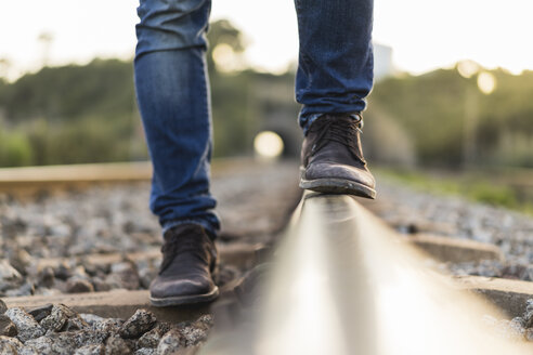Young man standing on railroad track - AFVF00483