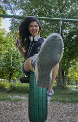 Portrait of happy young woman on a swing - BEF00088