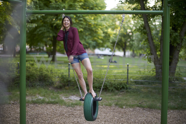 Laughing young woman having fun on a swing - BEF00091