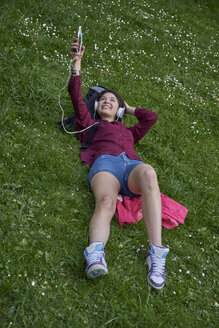 Young woman lying on a meadow listening music with headphones and cell phone - BEF00094