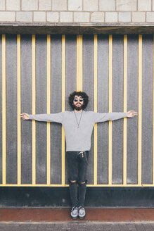 Portrait of young man, arms outstretched, in urban environment - CUF11414