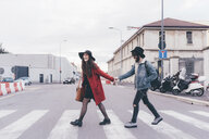 Young couple crossing road, holding hands, laughing - CUF11435