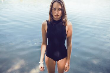 Portrait of woman wearing swimsuit standing in water looking at camera - CUF11447