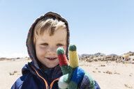 Portrait of cute boy making peace sign with gloved hand at Mount Teide, Tenerife, Canary Islands - CUF11486