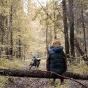 Woman on fallen tree in forest, motorbike in background, Ural, Bashkortostan, Russia - CUF11501