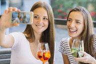 Two young female friends taking smartphone selfie at sidewalk cafe - CUF11504