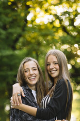 Portrait of two young female friends hugging in park - CUF11513