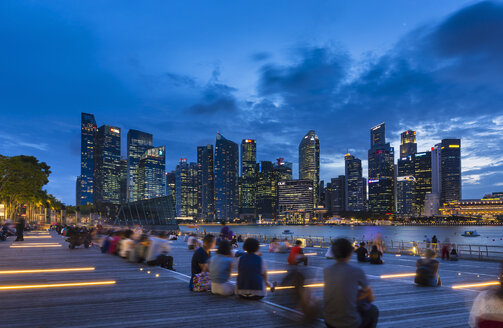 Tourists looking at city skyline from waterfront at dusk, Singapore, South East Asia - CUF11608