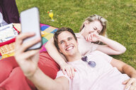 Group of friends relaxing on picnic blanket, in park, man taking selfie using smartphone - CUF11743