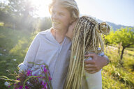 Romantic young couple with wildflowers in field, Majorca, Spain - CUF11806