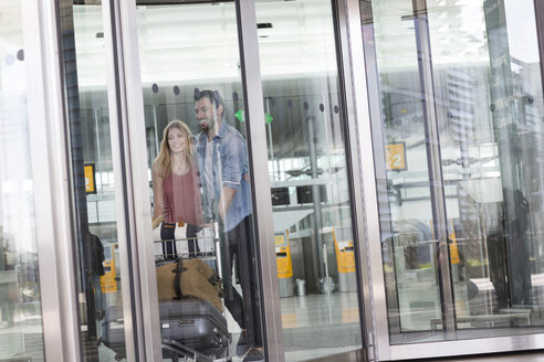 Young couple with luggage trolley in airport terminal - CUF11830