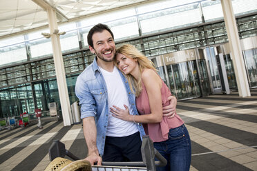 Young couple with luggage trolley arriving from airport terminal - CUF11833