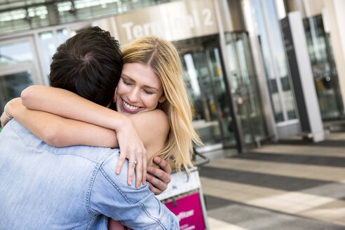 Young couple hugging outside airport terminal - CUF11836