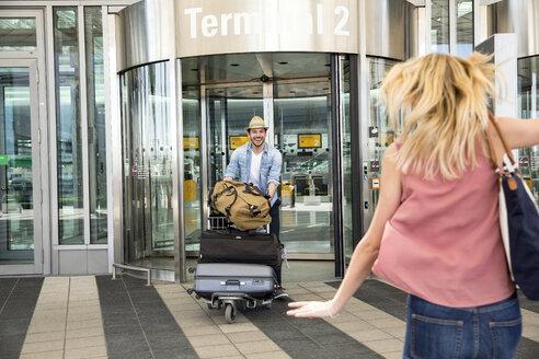 Young woman running toward boyfriend outside airport terminal - CUF11839