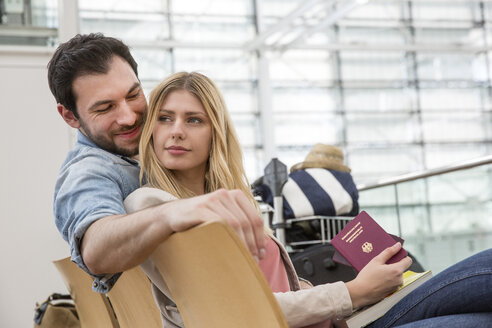 Young couple with passports waiting in airport departure lounge - CUF11842