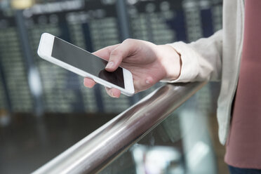 Hand of young woman holding smartphone in airport departure lounge - CUF11845