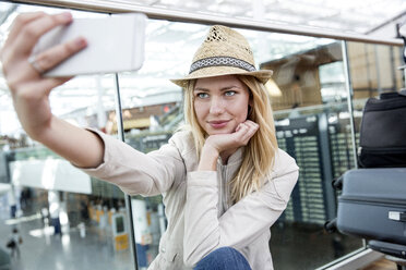 Young woman taking smartphone selfie in airport terminal - CUF11848