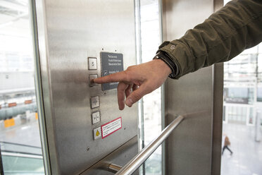 Man's finger pressing lift button at airport - CUF11851