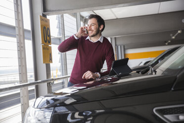 Young man making smartphone call in airport carpark - CUF11857