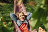 Portrait of smiling girl relaxing in hammock - ANHF00043