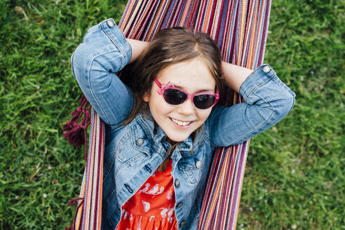 Portrait of smiling girl wearing sunglasses lying in hammock - ANHF00046