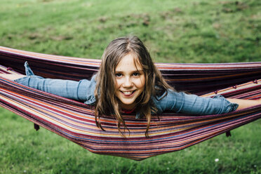 Portrait of smiling girl lying in hammock sticking out tongue - ANHF00049