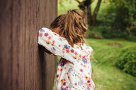 Girl leaning against wooden wall hiding her face - ANHF00058