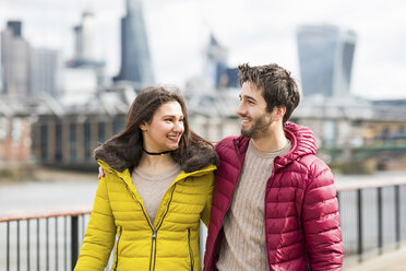 UK, London, young couple walking arm in arm on a bridge - WPEF00276