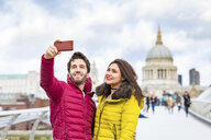 UK, London, portrait of smiling young couple taking selfie with cell phone in front of St Pauls Cathedral - WPEF00279