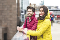 UK, London, young couple with coffee to go standing on bridge - WPEF00282