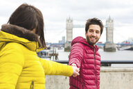 UK, London, portrait of smiling young man standing hand in hand on bridge over the Thames with his girlfriend - WPEF00288