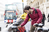 UK, London, young man renting bicycle from bike share stand in city - WPEF00291