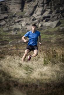 Male runner running down from Stanage Edge, Peak District, Derbyshire, UK - CUF11863