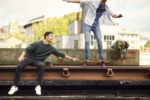 Two young men fooling around by train track, balancing on skateboard Bristol, UK - CUF11887