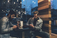 Two young male hipsters at sidewalk cafe looking at smartphones at night - CUF12052